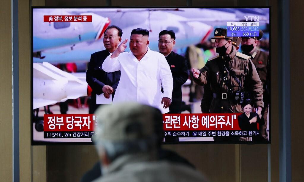 圖為民眾觀看電視新聞畫面,為北韓中央通信社12日報導,金正恩視察航空與防空所屬殲襲機團。(圖/美聯社)