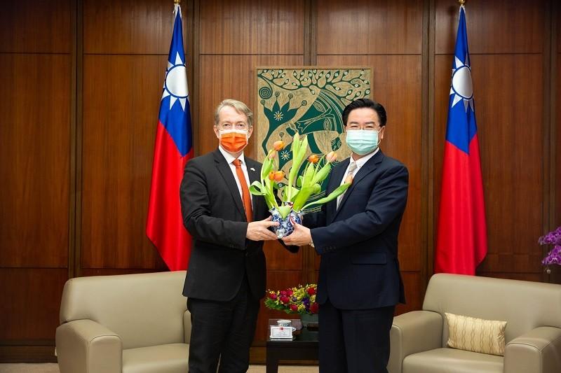 外交部長吳釗燮接受荷蘭駐台代表紀維德(左)致贈荷蘭國花鬱金香。圖/荷蘭貿易暨投資辦事處(荷蘭在台辦事處)