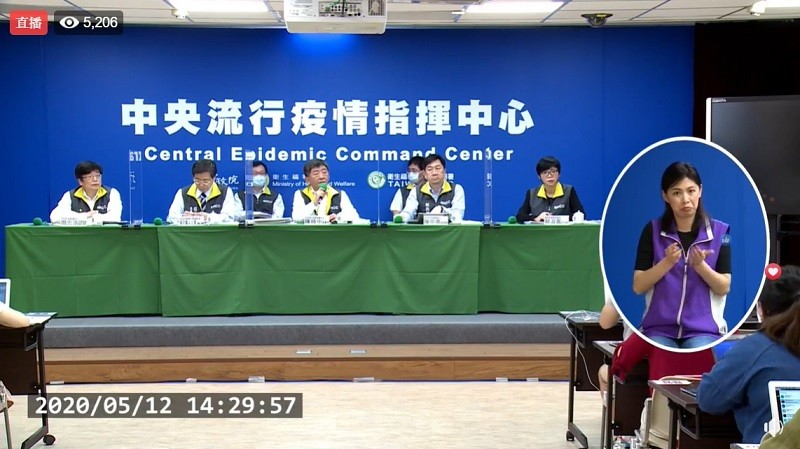 指揮中心5/12記者會示範以隔板拉開前排五人的社交距離, 包括陳時中在內的5人在此情況下可不戴口罩 (直播截圖)