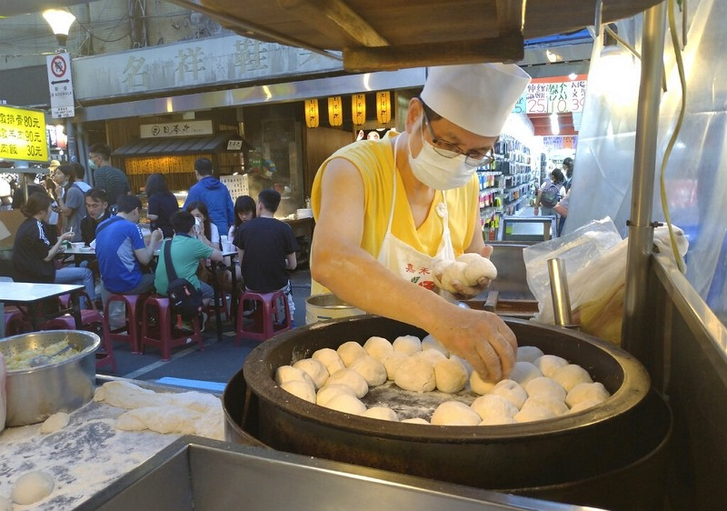 Vendor wears face mask to protect against coronavirus as he cooks grilled pork buns at Taipei night market.