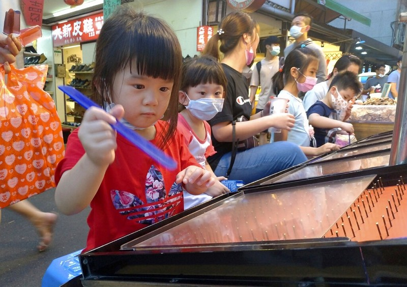 Children wear face masks to help curb the spread of the coronavirus as they play carnival games at a night market in Taipei.