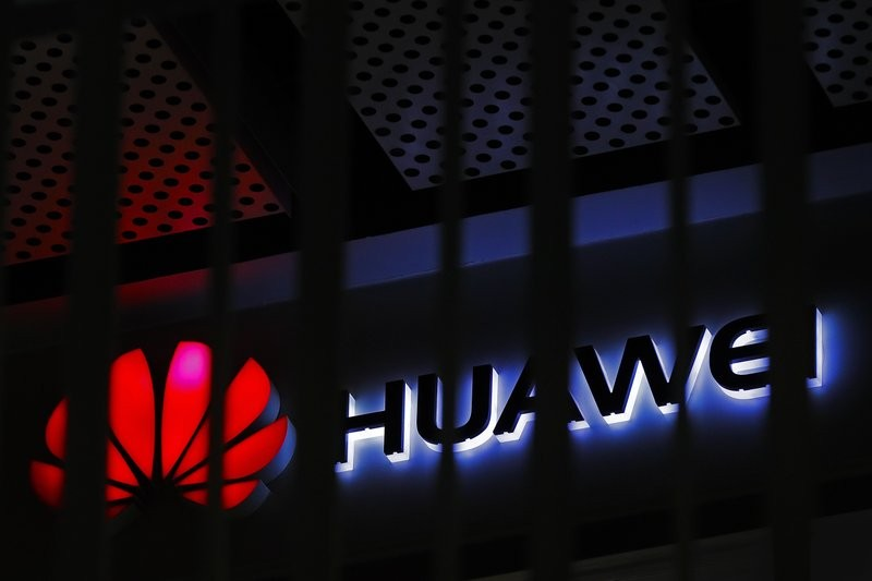 In this March 8, 2019, file photo, alogo of Huawei retail shop is seen through a handrail inside a commercial office building in Beijing.