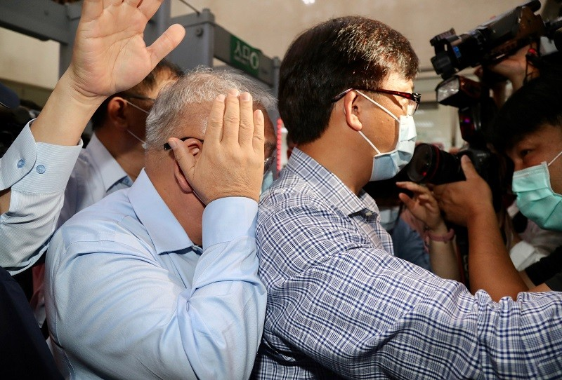 錢櫃董事長練台生(前左),22日訊後被諭令以新台幣100萬元交保。練台生離開北檢時媒體蜂擁而上,練台生則以手遮臉,躲避拍攝。中央社
