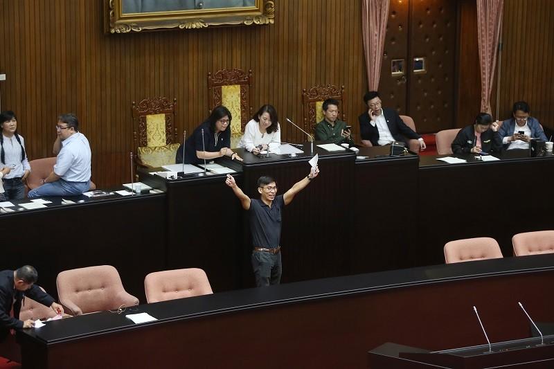 民進黨立法院黨團書記長鍾佳濱(高舉雙手者)26日一早率領黨籍立委占據主席台,先行反制國民黨抗議行動,確保能順利投票。中央社