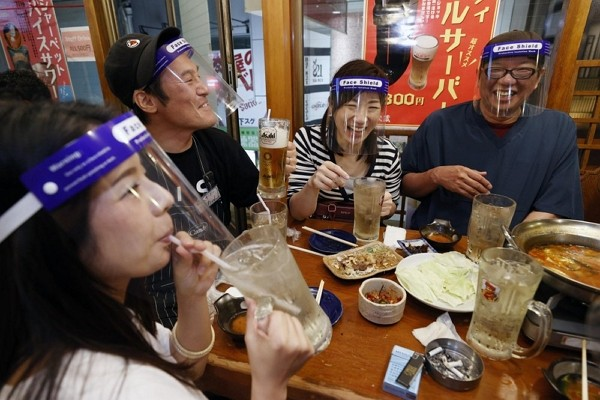 People wearing face shield, eat together at a pub in Osaka, western Japan Monday, May 25, 2020 as Japan has lifted the coronavirus state of emergency ...