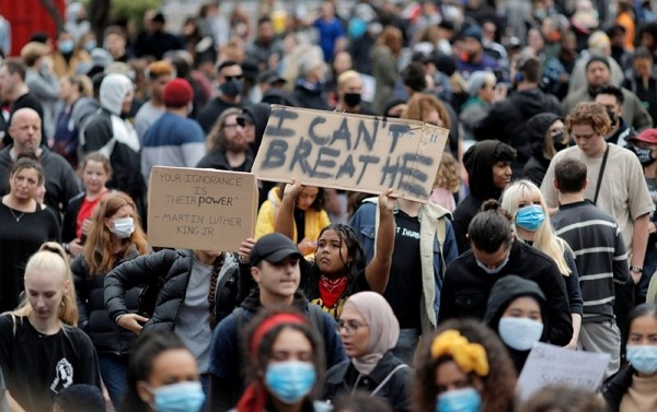 Demonstrators hold placards during a march in central Auckland, New Zealand, Monday to protest the death of United States' George Floyd, a black m...