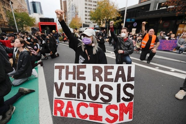 Demonstrators gesture during a march in central Auckland, New Zealand to protest the death of United States' George Floyd, a black man who died in...