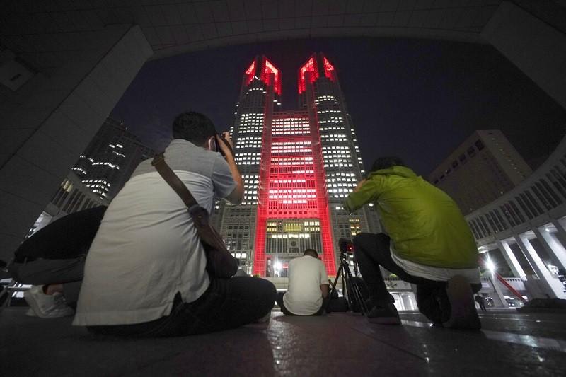 東京都政府大樓2日晚間也亮起紅燈, 提醒民眾注意防疫警戒 (美聯社)