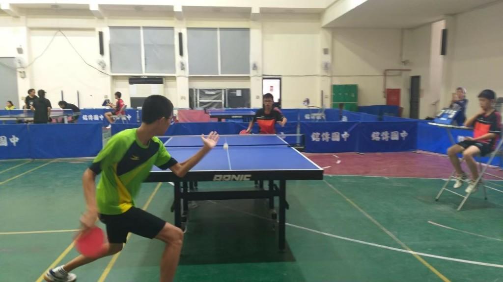 (說明:楊博崴(綠色運動服者)參加桌球賽事時,專心打球的英姿)