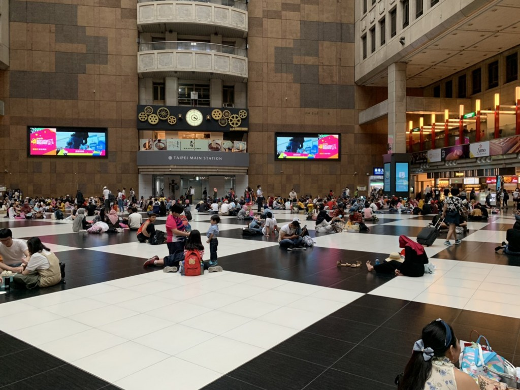 Migrant workers seen sitting on floor of Taiwan Main Station on Sunday, June 7.