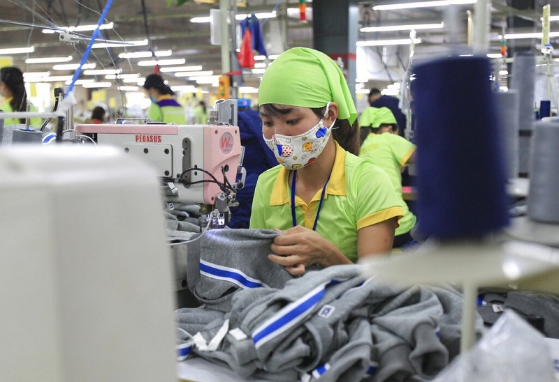In this Oct. 24, 2017, file photo, a worker sews a garment at Pro Sports factory in Nam Dinh province, Vietnam.