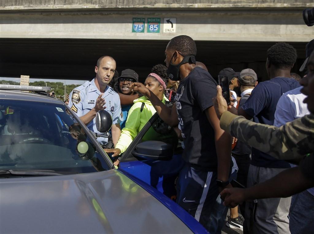 美國喬治亞州亞特蘭大12日晚間發生非裔男子布魯克斯拒捕遭警擊斃事件,引發民眾怒火上街抗議。圖為示威民眾在事發地點附近與警方發生口角衝突。(...