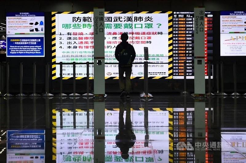 圖為民眾在桃園機場電子看板前觀看疫情警語。(中央社檔案照片)