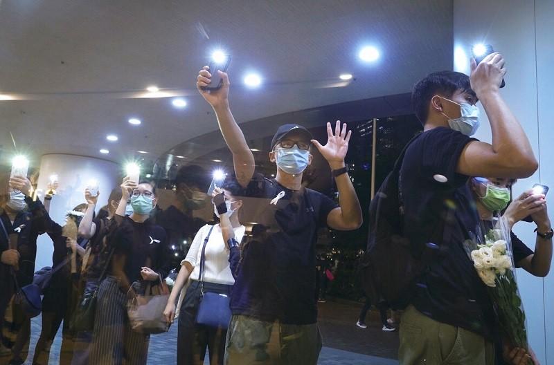 圖為今年6月15日,港人用手機閃光燈紀念2019年6月15日,反送中示威者梁凌杰,在金鐘太古廣場墜樓身亡一周年。美聯社
