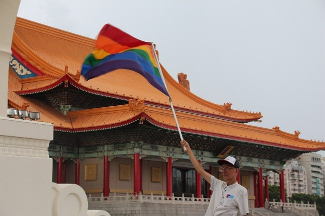 Chyi Jia-uei (祁家威) waves rainbow flag at rally with National Concert Hall in background.