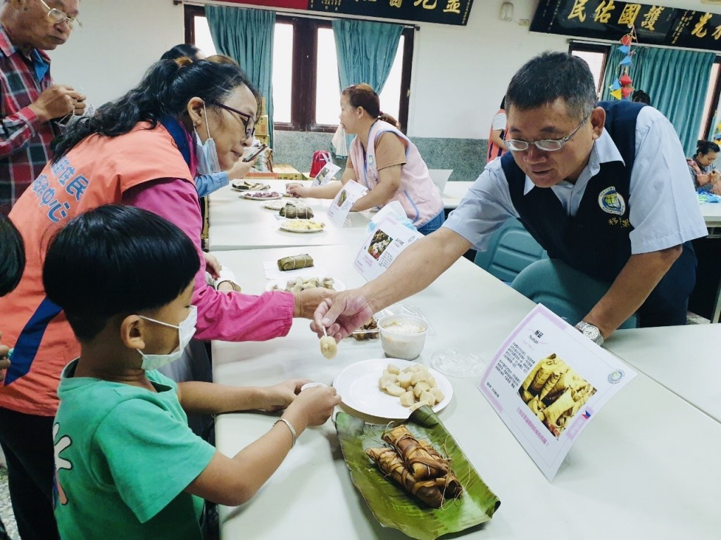 雲林縣服務站專員吳景賢請到場參與的新二代吃異國風味粽子(圖/ 移民署雲林縣服務站)