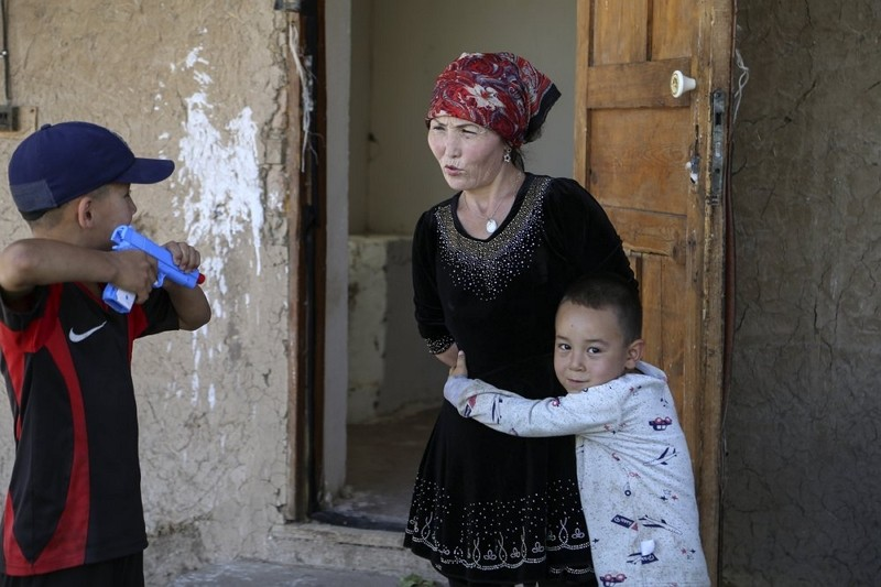 Alif Baqytali hugs his mother, Gulnar Omirzakh, at their new home in Kazakhstan. Omirzakh, a Chinese-born ethnic Kazakh, says she was forced to get an...