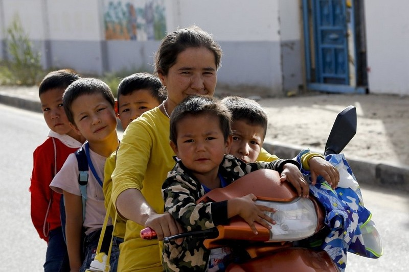 In this Sept. 20, 2018 file photo, a Uighur woman and children sit on a motor-tricycle after school at the Unity New Village in Hotan, Xinjiang.