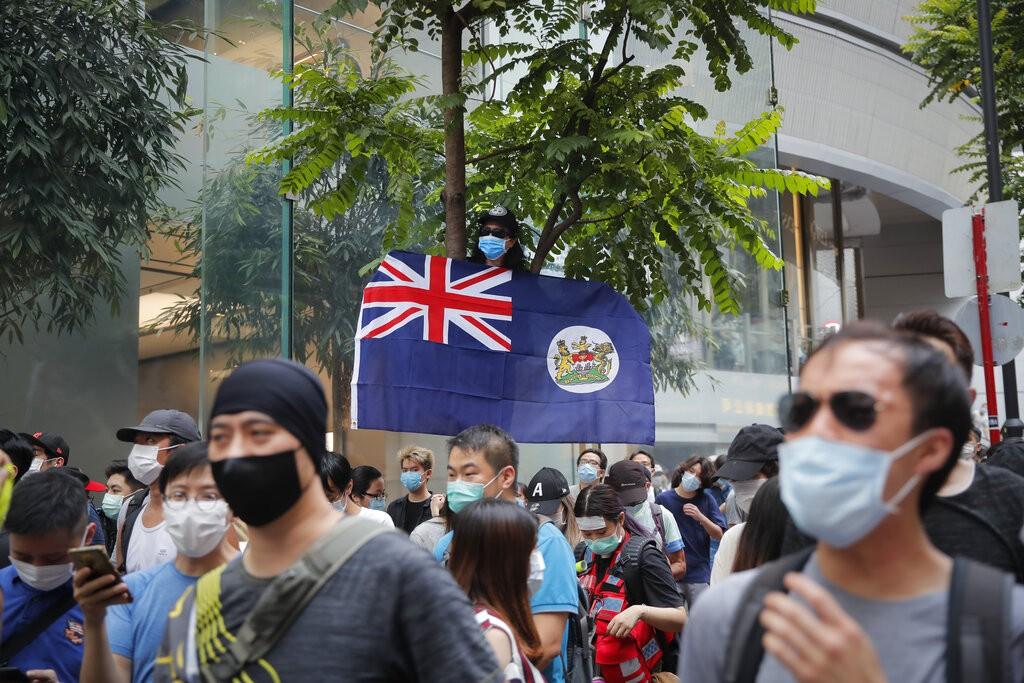 A man displays the Hong Kong colonial flag on the anniversary of Hong Kong's handover to China from Britain in Hong Kong, Wednesday, July. 1, 2020...