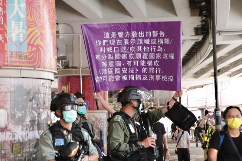 「港區國安法」生效,港警1日面對自行上街「七一」遊行的群眾,首度舉出了象徵執行此法的紫色旗幟。中央社