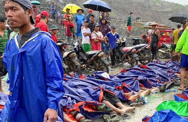 People gather near the bodies of victims of a landslide near a jade mining area in Hpakant, Kachine state, northern Myanmar Thursday, July 2, 2020.&nb...