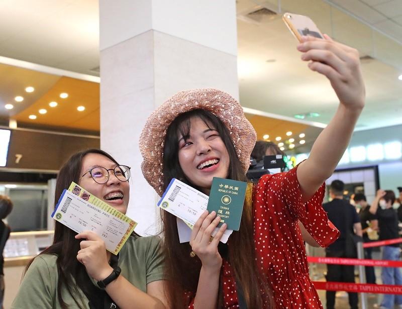 台北松山機場2日舉辦偽出國活動,旅客在領取登機證後開心自拍留念。(中央社)