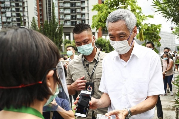People's Action Party Secretary-General and Singaporean Prime Minister Lee Hsien Loong, right, verifies his identity with a polling official at th...