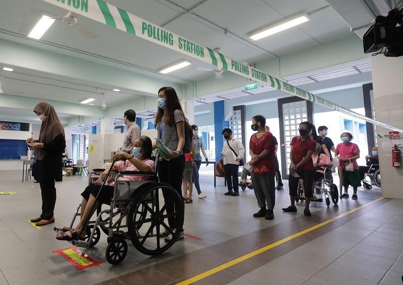 新加坡10日在疫情下舉行國會大選,選民進入投票站前要量體溫,也須保持社交安全距離。中央社