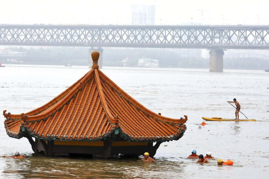 Residents swim past a riverside pavilion submerged by the flooded Yangtze River in Wuhan.