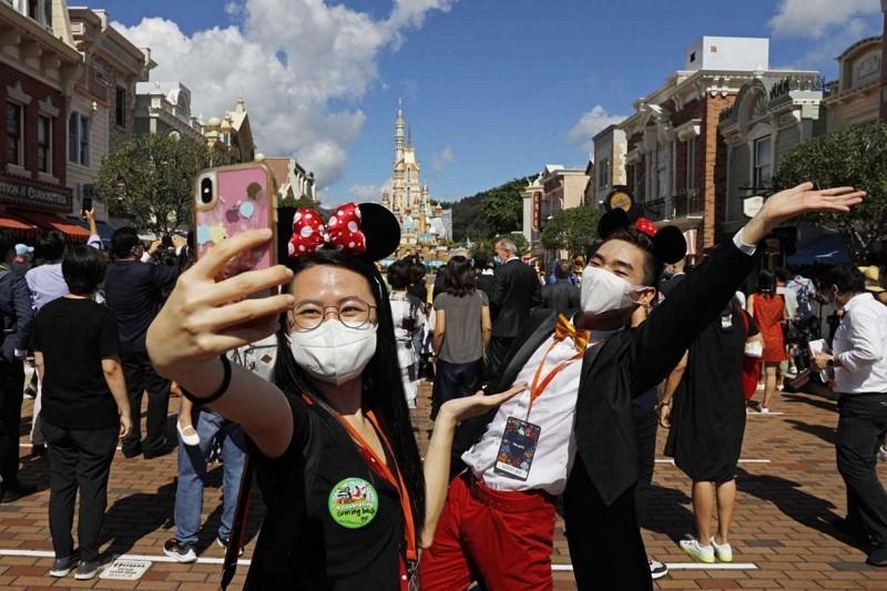 Visitors take selfieat Hong Kong Disneyland June 18, 2020.