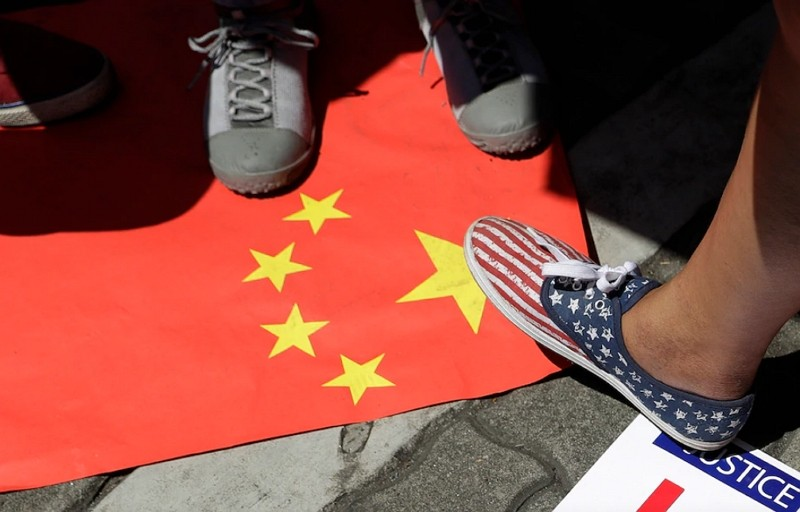 In this June 21, 2019, file photo, protesters step on a Chinese flag during a rally outside the Department of Foreign Affairs in Manila.