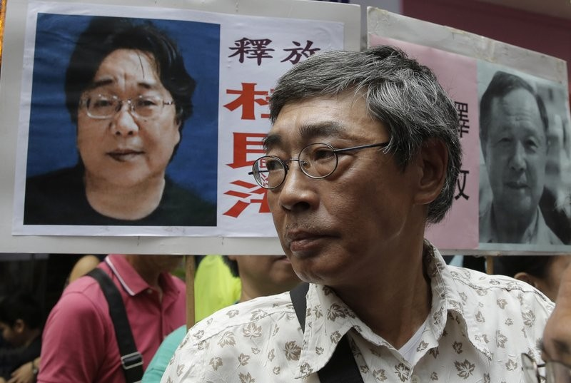 Lam Wing-kee stands next to placard with picture of missing bookseller Gui Minhai.