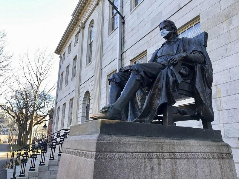 哈佛大學校內知名的約翰·哈佛雕像, 在武漢肺炎疫情期間, 也被人戴上了口罩 (美聯社檔案照片)