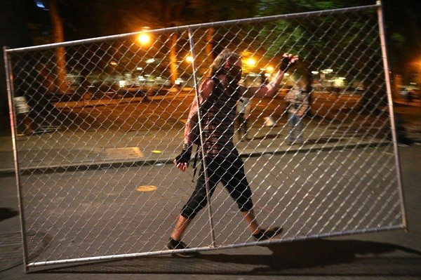 Protesters relocate a fence in front of the Justice Center, Saturday, July 18, 2020, during another night of protests in Portland, Ore.
