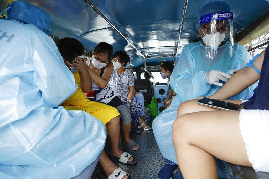 Health workers collect blood samples inside a jeepney bus.