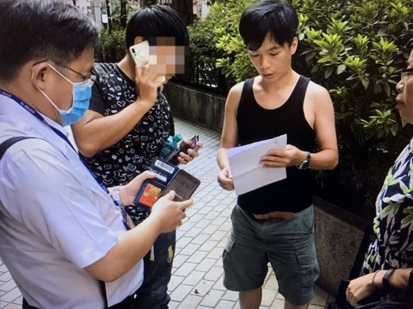 Li (second from left) detained for refusing to pay quarantine violation fines.