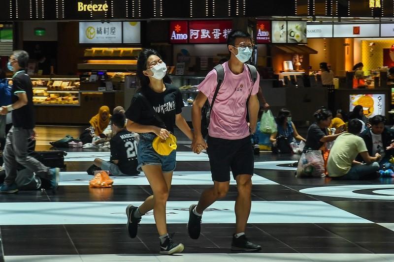圖為台北車站內,民眾戴口罩防疫。 (中央社)