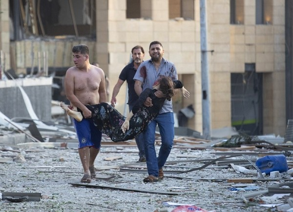 Wounded people are evacuated after a massive explosion in Beirut, Lebanon, Tuesday, Aug. 4, 2020.