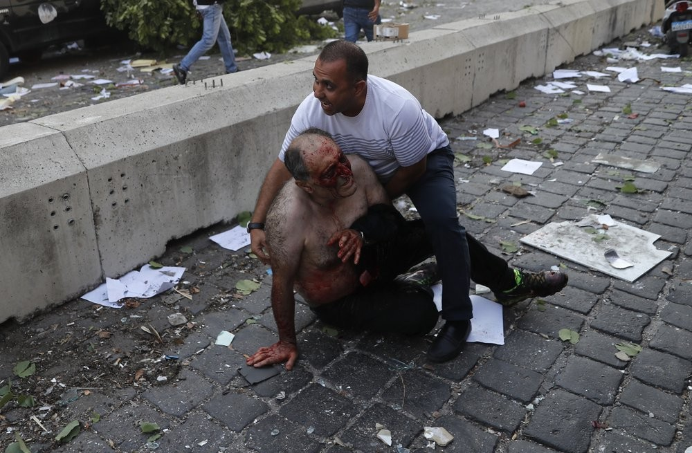 Lebanese man helps an injured man who was wounded by an explosion that hit the seaport, in Beirut Lebanon, Tuesday, Aug. 4, 2020.
