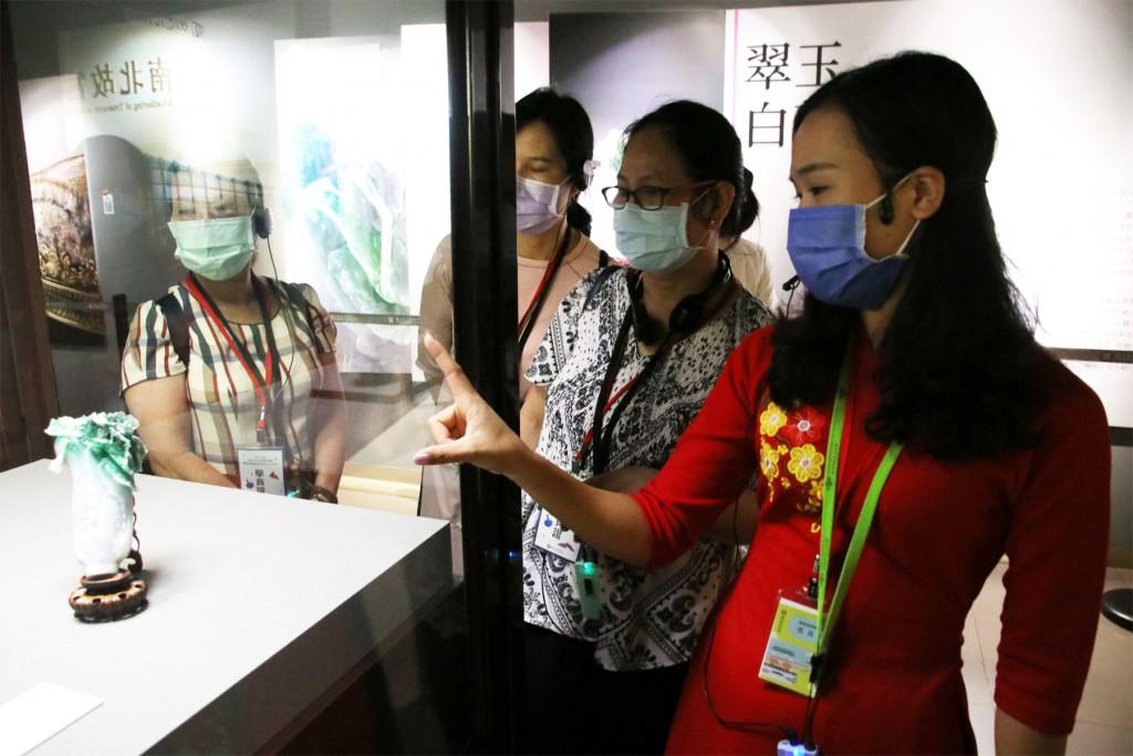 越南新住民范氏月(右1)指出翠玉白菜只有18公分高,但卻雕工精細,令人陶醉。(圖/ 移民署台北市服務站)