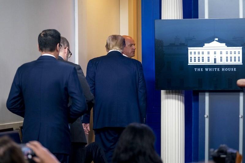 美國總統川普由特勤人員護送離開記者會(圖/美聯社)