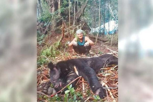 Ho posing with bear carcass. (Forestry BureauHsinchu ForestDistrictOffice photo)