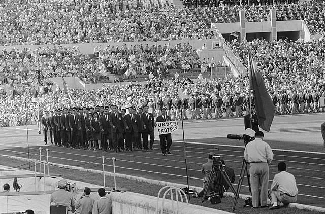 """1960年夏季奧林匹克運動會中華民國代表團進場,隊伍前可見林鴻遠舉著「Under Protest」的布條。(<a href=""""https:..."""