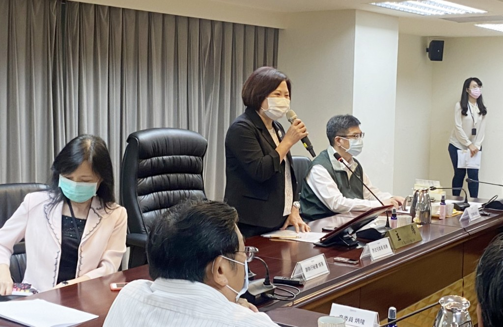 Labor Minister Hsu Ming-chun (center, standing) addresses the meeting which decided to raise the minimum monthly wage by 0.84%