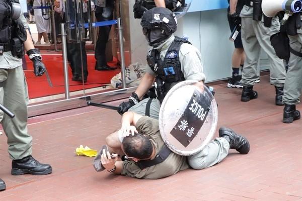 Hong Kong police officer with shield and baton straddles man.