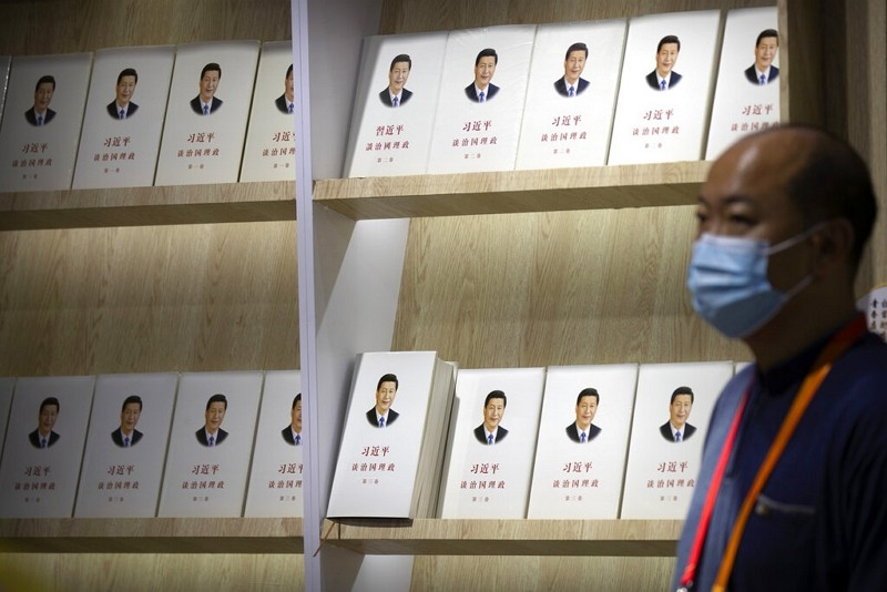 """A man wearing a face mask stands near a display of copies of the book """"The Governance of China"""" by Xi Jinping."""