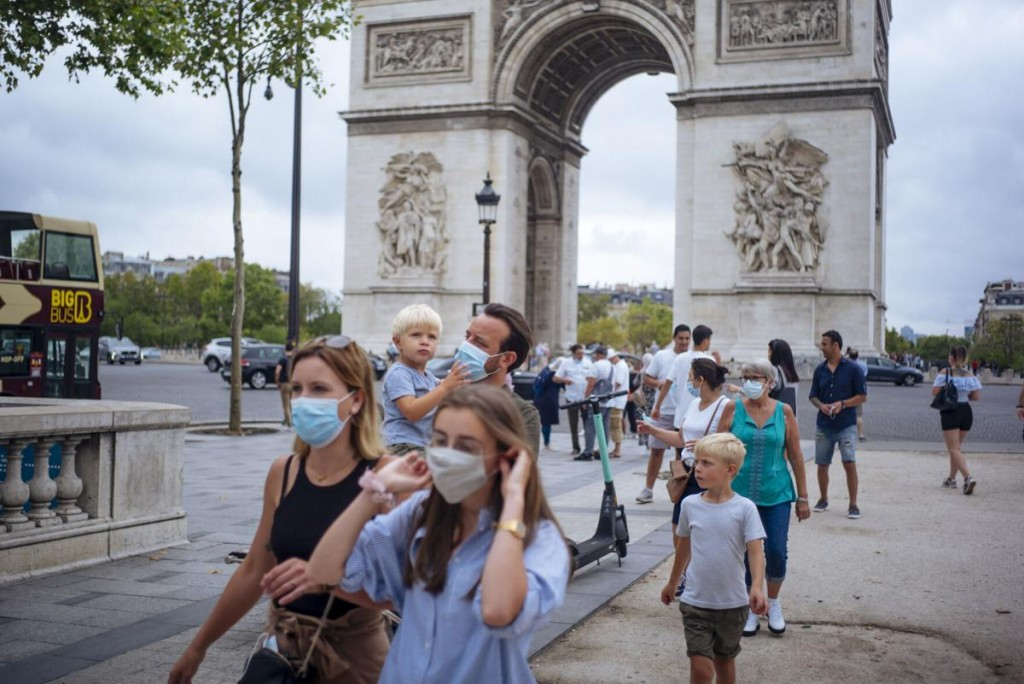 Family wearing protective face masks walk along the Champs Elysee Avenue, with Arc de Triomphe in background.