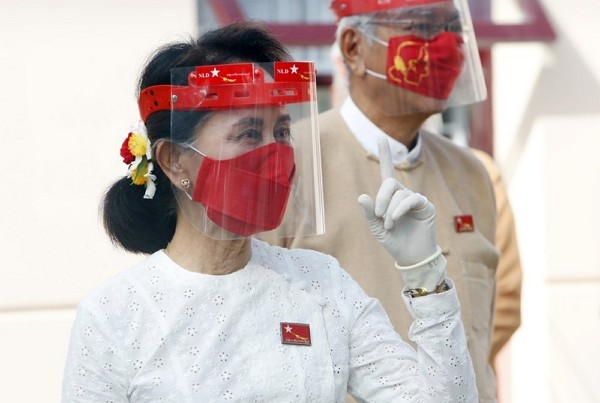 Myanmar leader Aung San Suu Kyi gestures while wearing a face shield, mask and gloves during a flag-raising ceremony to mark the first day of election...