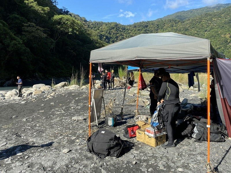南投仁愛鄉13日發生民眾露營被溪水沖走意外後,為尋找失蹤者,消防局人員在意外發生地點的野炊帳篷設立前進指揮所。中央社