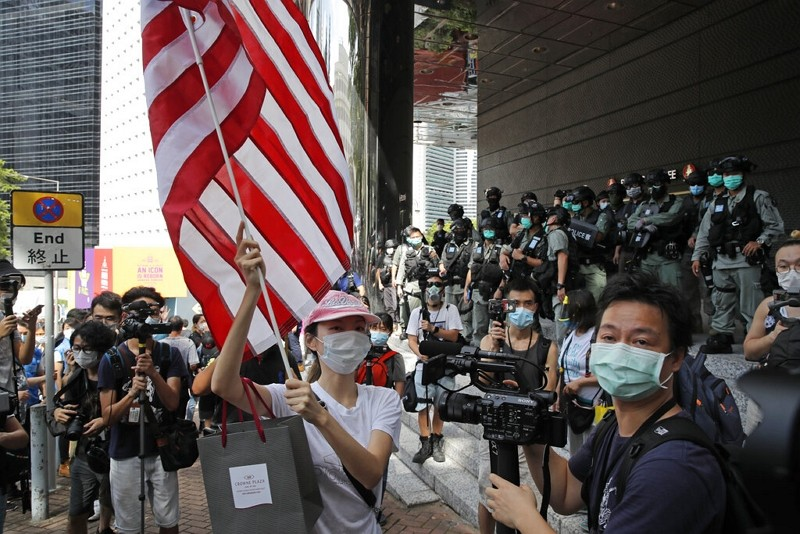 In this July 4, 2020, file photo, a woman carries an American flag during a protest outside the U.S. Consulate in Hong Kong.